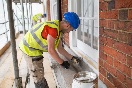 workman repairing window frame